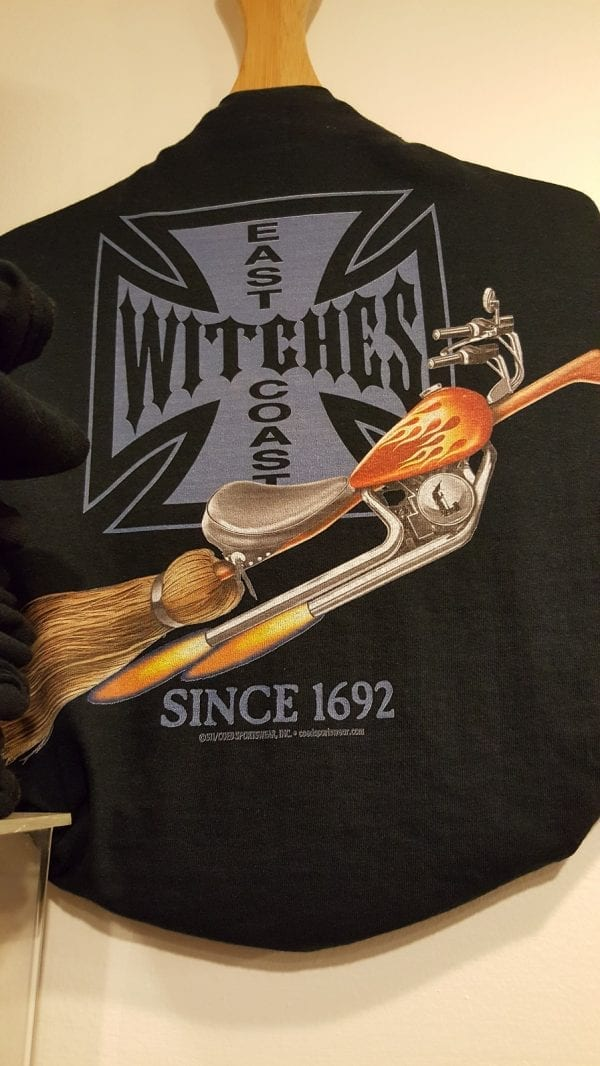 """A broom styled lika a motorcycle on a black background. Text reads """"east coast witches."""""""