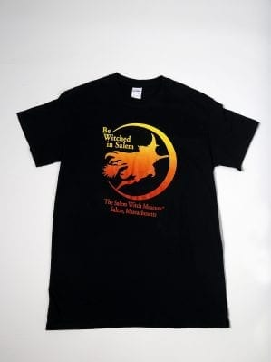 "A black t-shirt with an orange witch. Reads ""Be Witched in Salem"""