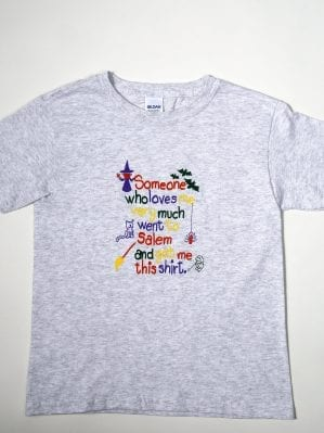 "A grey youth t-shirt reading ""Someone who loves me very much went to Salem and got me this shirt."""