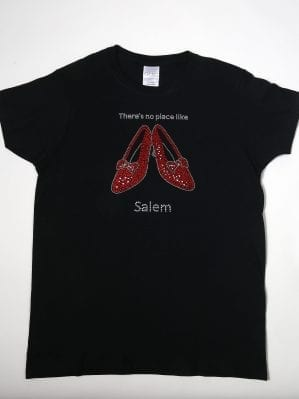 "Black t-shirt with rhinestone ruby slippers and text saying ""There's no place like Salem"""