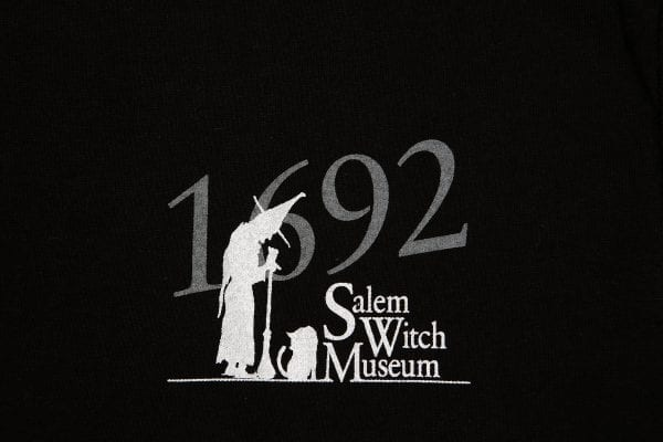 The Salem Witch Museum logo in grey and white.