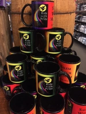 black mug with rainbow wrap. Reads Salem Witch Museum. has witch flying in front of moon trailing a rainbow. says Ride with Pride
